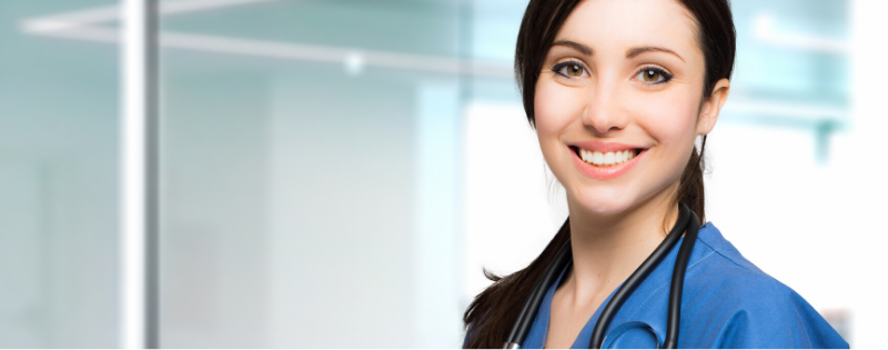 Brown Haired Nurse Smiling in Dark Blue Scrubs