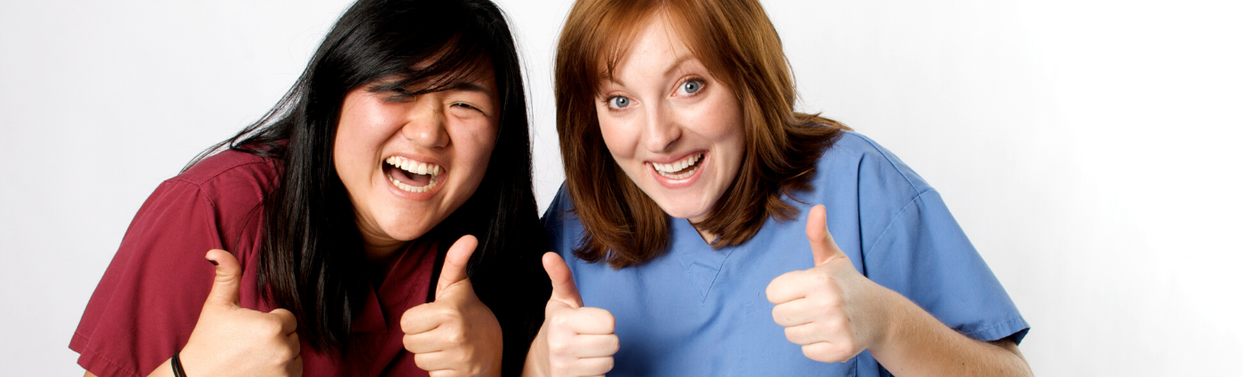 Two Nurses With Thumbs Up and Smiling